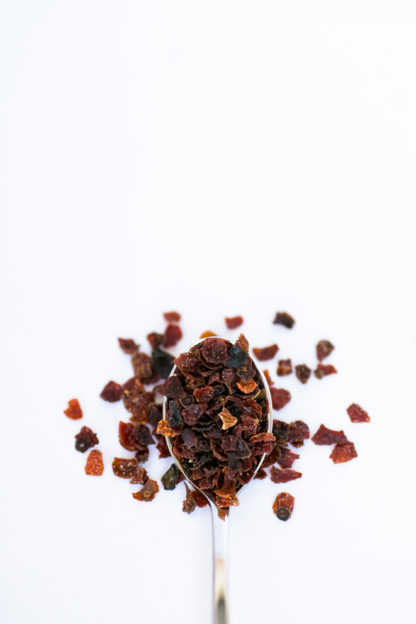 Deep red half round dried skins from rose hips overflow the silver spoon onto a white background