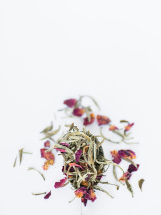 Dark red and orange rose petals blend with light green and white tea needles spilling over the silver spoon onto the white background