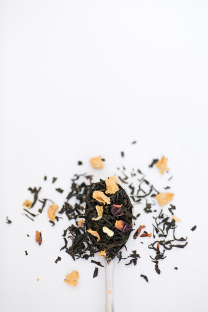 Dark brown black tea leaves blended with lotus flower petals and orange peel cascade over the silver spoon onto the white background