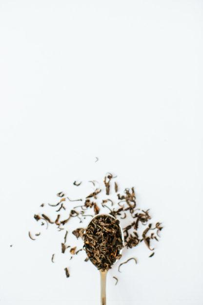 Dark golden brown black tea leaves spill over the spoon onto the white background