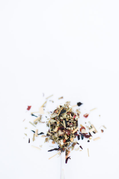 Fluffy green raspberry leaf, red rose hips, light yellow lemon grass and hibiscus flower petals overflow the silver spoon onto a white background