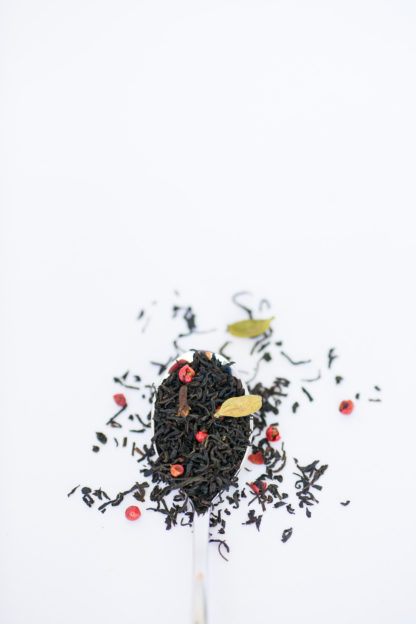 Dark brown black tea leaves, bright red peppercorns, light green cardamom pods and clove pieces overflow the silver spoon onto the white background