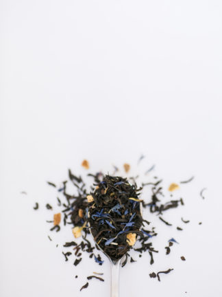 Bright orange peel pieces, corn flowers, and cloves blended with dark brown black tea leaves spilling over the silver spoon onto the white background