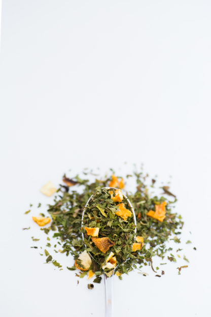 Bright chopped orange skin pieces blended with bright green chopped mint leaves spill over onto a white background