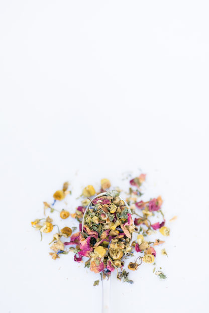 Light yellow chamomile dried florets sprinkled with red rose petals, chopped mint leaves, anise star piedces and seeds flow over the spoon onto a white background