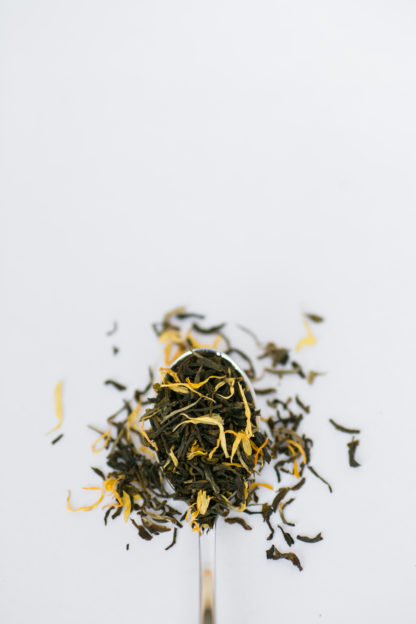 Bright yellow marigold flower petas blend with dark green tea leaves flow over the silver spoon onto the white background