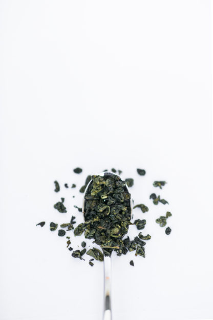 Dark green clumped tea leaves spilling over the silver spoon onto the white background
