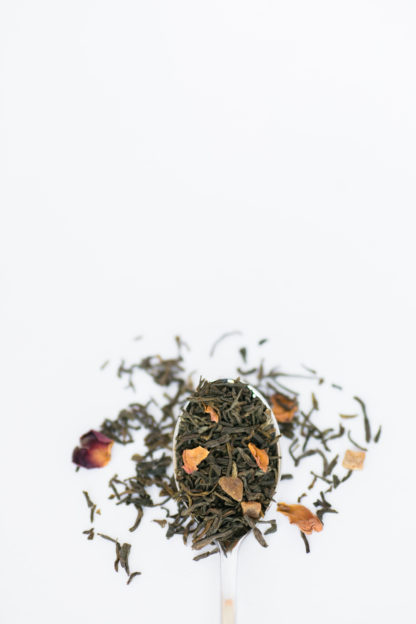 Deep red and organge rose petals are blended into dark green tea leaves spilling over the spoon onto the white background
