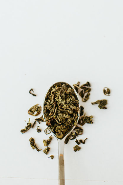 Varigated brown and green classically clumped oolong tea leaves spill over the edge of the silver spoon onto the white background