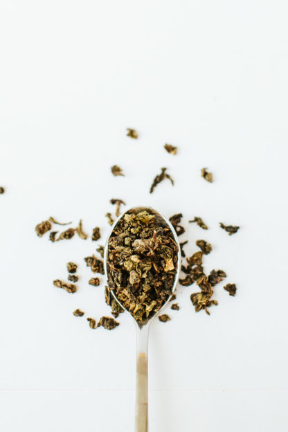 Varigated green and brown classic clumped oolong tea leaves spill over the edge of the silver spoon onto the white background