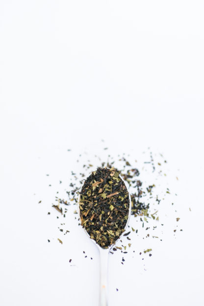 Finely chopped black tea leaves blended with dark green mint pieces overflow the silver spoon onto the white background