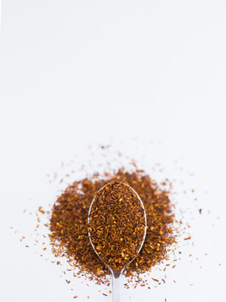 Dark red chopped rooibos with orange flakes spooned onto a white background