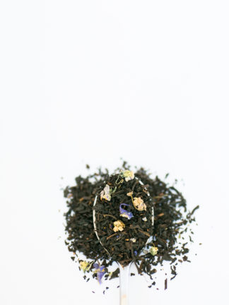 Dark black tea leaves sprinkled with violet flower petals and currents overflow the spoon onto the white background