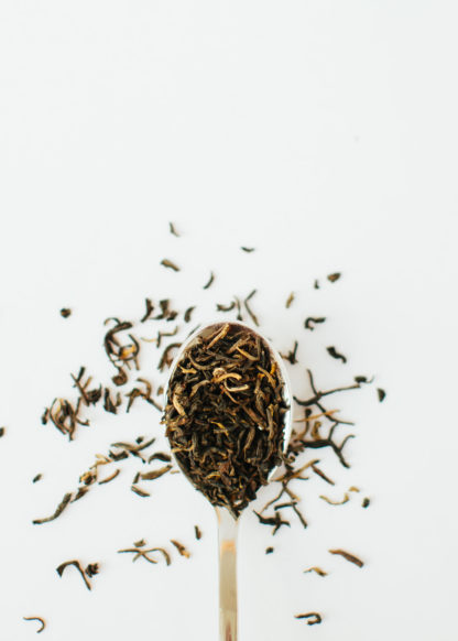 Rich orange tendril-like tea buds blended in a rusty orange black tea in a silver spoon overflowing on a white background