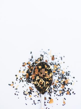 Black tea with white coconut pieces, cardamom, cinnamon bark chips, cloves, and more Middle-Eastern spices spill over the silver spoon onto the white background