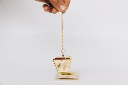 Golden lantern shaped loose leaf tea infuser on chain with cup rim hook suspended above a gold saucer on white background