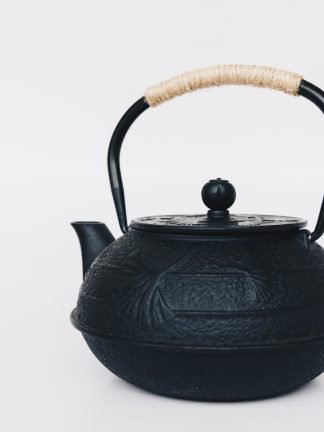 Black cast iron rounded teapot with lotus leaf pattern on surface, short curved spout and heavy duty cast iron arching handle wrapped with tan cord on white background