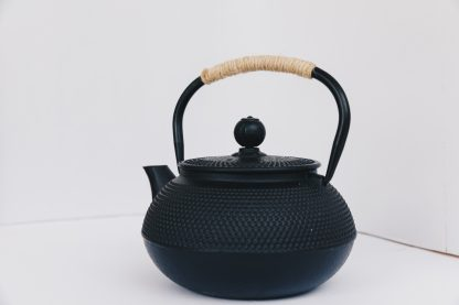 Black cast iron rounded teapot with stippled pattern on surface, short curved spout and heavy duty cast iron arching handle wrapped with tan cord on white background