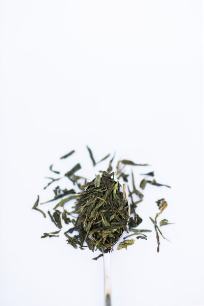 Flat dried green tea leaves overflow a silver spoon onto a white background
