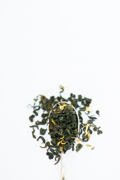 Dark green clumped loose leaf tea leaves mixed with safflowers and mint cascading over a silver spoon on a white background