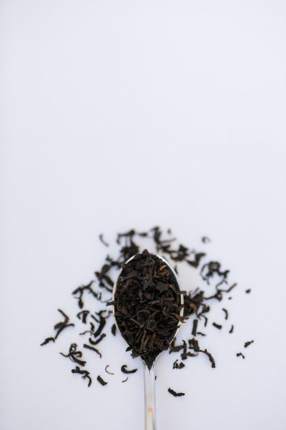 Small dark black tea leaves cascade from a silver spoon onto a white background