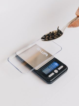 Small loose leaf tea scale with clear lid and tray for weighing teas to the .01 gram with silver tea spoon containing tea to be weighed on white background