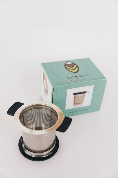 Stainless steel loose leaf tea infuser with black silicon support wings and lid/saucer with teal gift box on white background