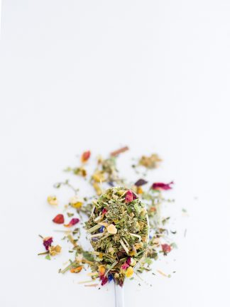 Beautiful dried chamomile florets blended with rose petals, lemon peal, lemon verbena, lemon grass overflow a silver spoon onto a white background