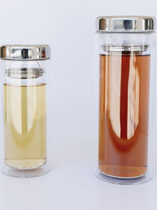 One 12 ounce and one 16 ounce clear glass double walled tea tumbler containing steeped green tea and steeped black tea with a stainless steep strainer separating the liquid and the stainless steel lid on a white background