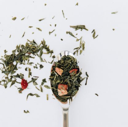 Green tea and strawberry pieces overflow the silver spoon onto a white background
