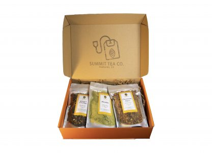 Orange flat gift box and hinged lid with a large rubber stamped Summit Teabag on the underside of the lid with 3 four ounce teas in bags slightly overlapping