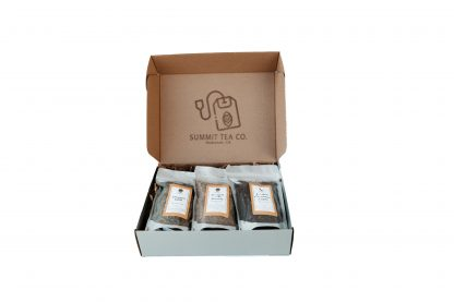 Silver grey flat gift box and hinged lid with a large rubber stamped Summit Teabag on the underside of the lid with 3 four ounce teas in bags slightly overlapping