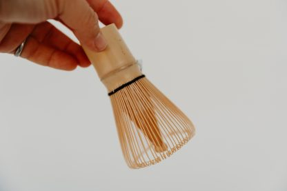 Hand holding a bamboo matcha whisk